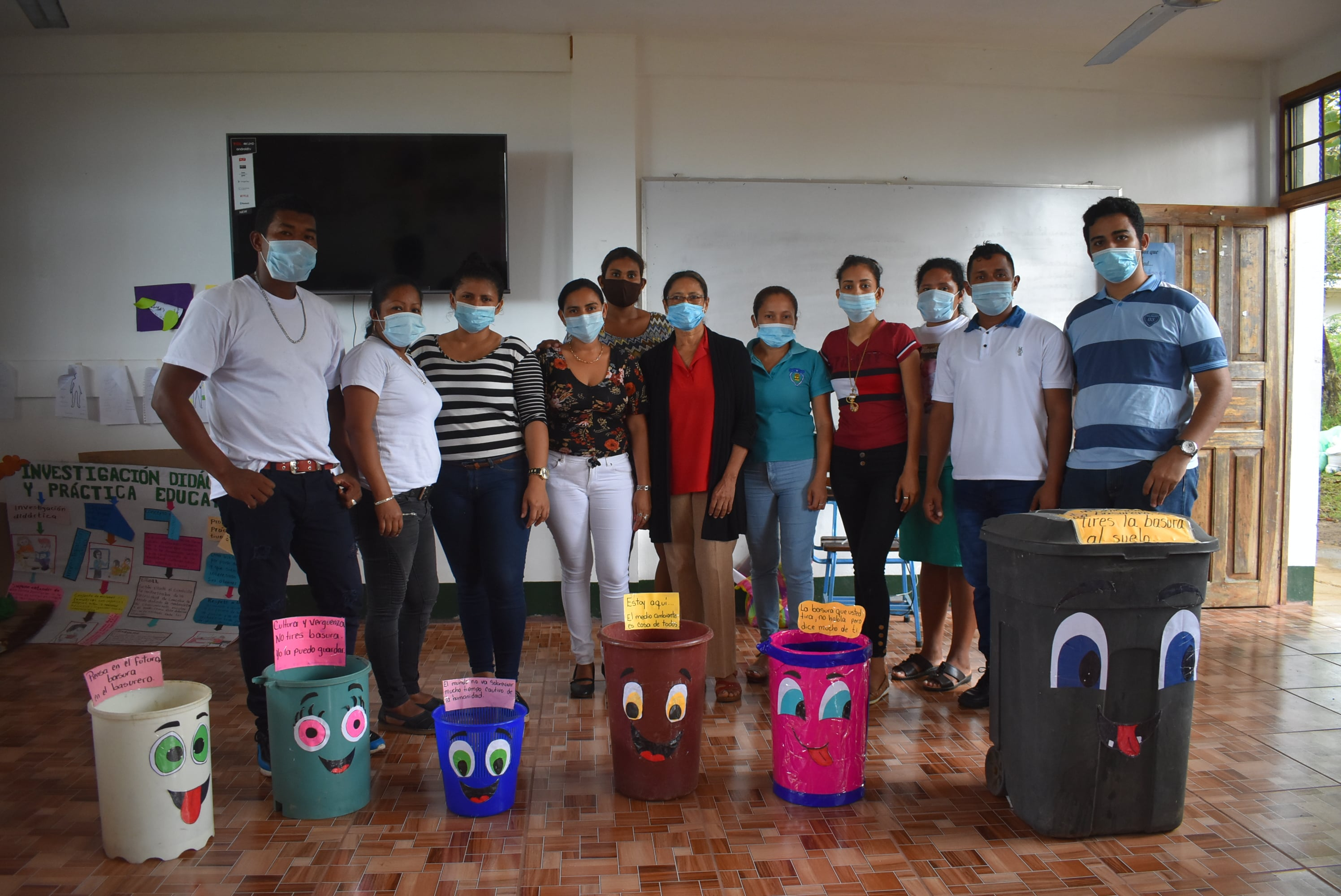 Students of URACCAN Bluefields enclosure decorating trash cans with environmental and eye-catching messages,